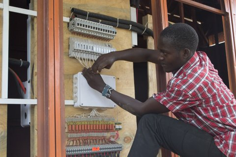 A young Kenyan ICT technician at a solar power hub in Kajiado county south of Nairobi