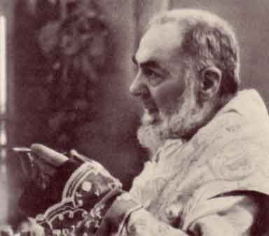 Padre Pio offering the host