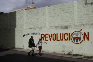 """Dos personas transitan al lado de una cartel en el que puede leerse la frase """"En cada barrio revolución"""", en una calle de Centro Habana, en la capital de Cuba, que resalta la importancia de cada asentamiento para el poder político del país."""