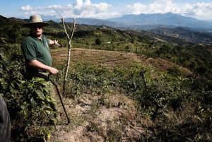 Donald Vásquez shows how the land has been degraded in an area of coffee plantations on the slopes of Berlin, one of the towns in the Barranca-Jesús María river basin in western Costa Rica. Farmers in the area, with the support of experts, have built terraces and channels to curb erosion. Credit: Miriett Ábrego / IPS