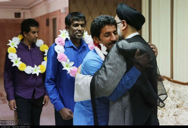 "Iran's Intel Minister Mahmoud Alavi hugs the recently freed hostages in Tehran on ""Friday""."