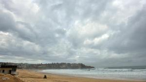 """Storm clouds gather over Sydney's Bondi Beach as the city battles cyclonic wind gusts and non-stop downpours on April 22, 2015. Heavy rain and high winds battered Sydney and other areas for a third day causing widespread chaos, with emergency services dealing with nearly 10,000 calls for help and a """"cruise from hell"""" finally docking. AFP PHOTO / Peter PARKS        (Photo credit should read PETER PARKS/AFP/Getty Images)"""