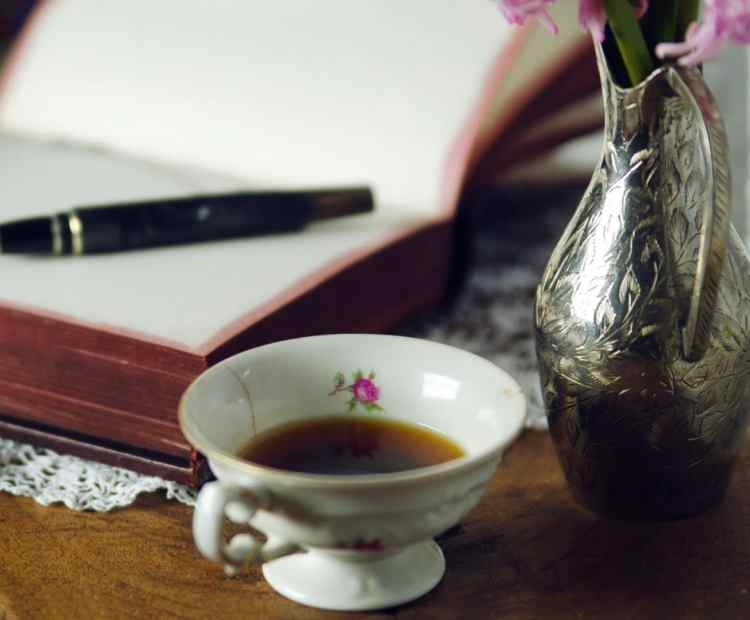 Cup Of Coffee And Open Notebook With Pen On Wooden Desk With Silver Vintage Vase