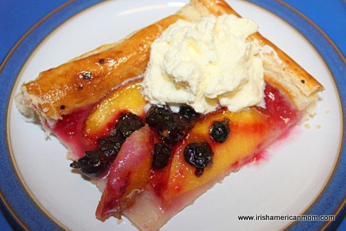 Slice of nectarine and blackcurrant galette with cream