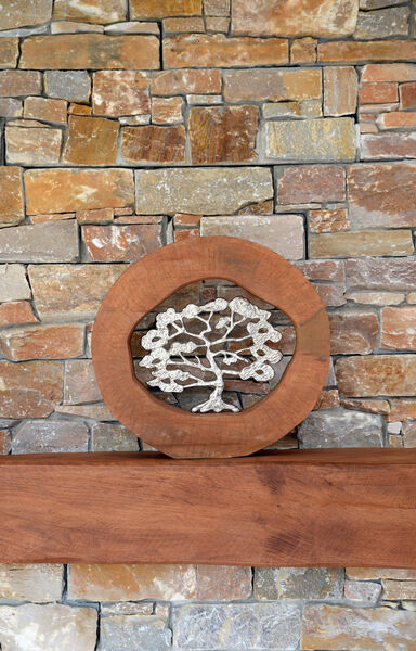 The circular wood/ metal wall art piece was a gift from a family member and its style works with the mantel style, both in the wood type and the chunky frame.