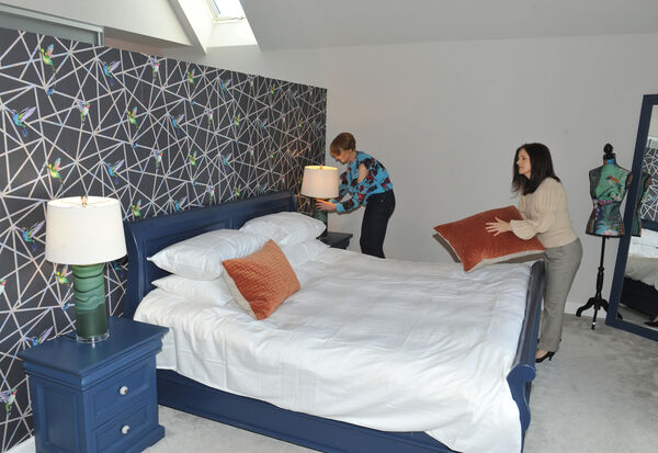 Interior designer Sinead Cassidy and Carol O'Callaghan check items and layout in the master bedroom.