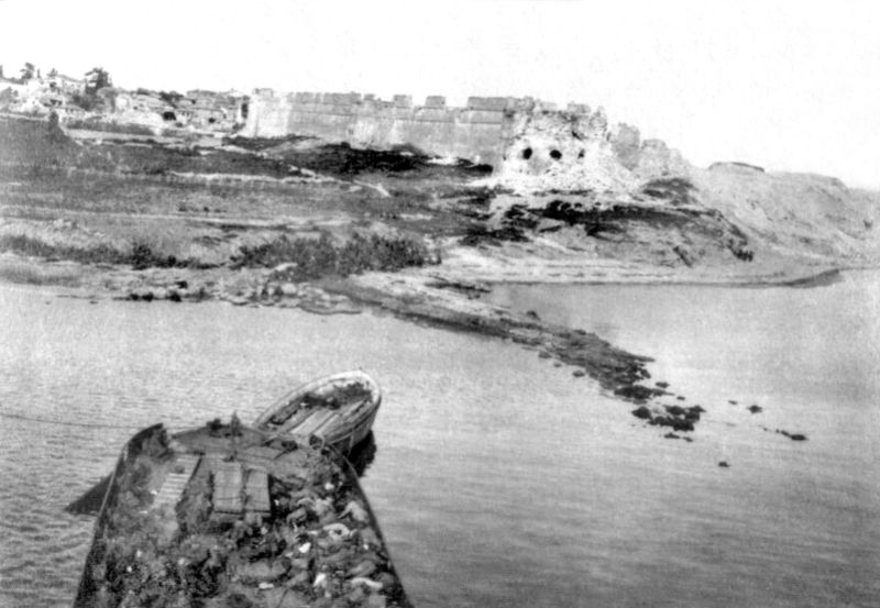 Sedd-el-Bahr fort and village seen from the SS River Clyde, 25 April 1915, during the landing at Cape Helles, Battle of Gallipoli. The lighter in the foreground contains dead from the Royal Munster Fusiliers and The Hampshire Regiment who were killed while attempting to get ashore. Public domain photo taken from http://en.wikipedia.org/wiki/File:Sedd-el-Bahr_from_River_Clyde.jpg