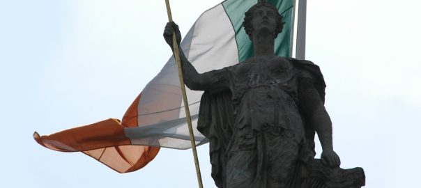 The statue of Hibernia that stands on the Dublin General Post Office, with an Irish flag in the background