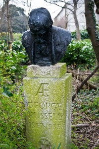 Bust of George Russell on an algae-stained stone plinth bearing the inscription: AE George Russell 1867-1935