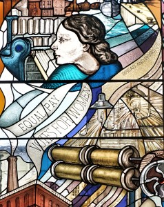 """Stained class window depicting mill machinery, a woman in profile and ribbons saying """"equal pay"""", """"votes for women"""", """"roses and bread"""" (slogans of suffrage and social justice movements)"""