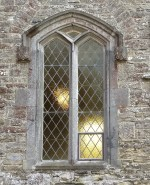 Arched window of diamond paned plain glass. The stone surround incorporates shields bearing a saltire