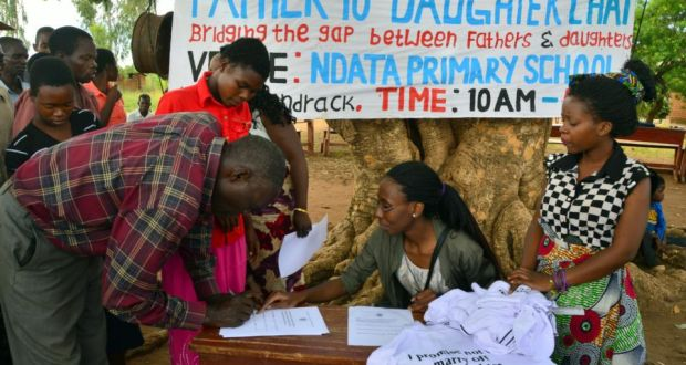 A father signs a document promising not to marry his daughter off during a fathers and daughters' 'chat day' in Chiradzulu district, Malawi. Photograph: Didem Tali