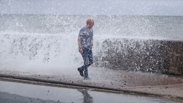 A man gets hit by a wave crashing on the Front Strand in Youghal, Co Cork. Photograph: Niall Carson/PA Wire