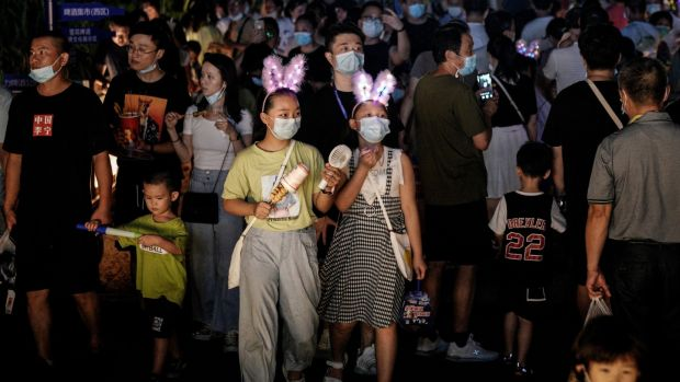 Residents wear masks while walking through the entrance to the Wuhan Beer Festival in China. Photograph: Getty Images