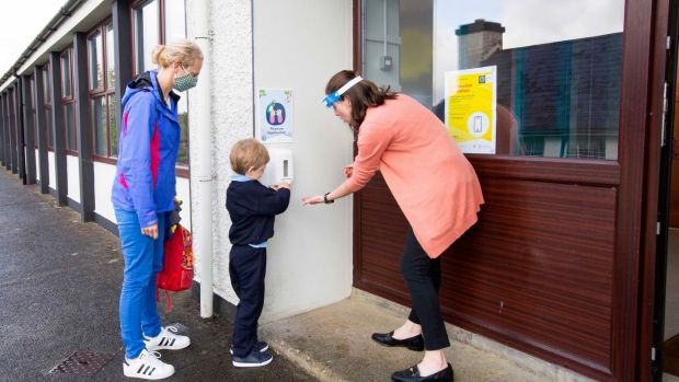 Ryan Gilrane sanitises his hands before entering school on his first day under the watchful eye of his mother, Christine, and teacher, Jacinta Greene. Photograph: Brian Farrell/The Irish Times