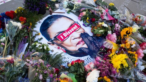 Flowers, candles and messages encircle an image of the late US Justice Ruth Bader Ginsburg, left by people that came to pay their respects for her outside the Supreme Court in Washington DC on September 19th. Photograph: Mchael Reynolds/EPA