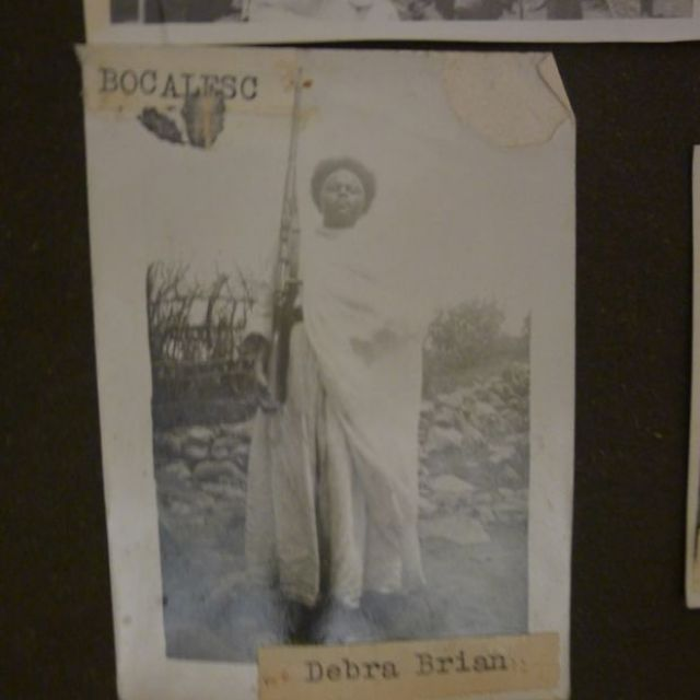 Bogalech from Debre Berhan is fully clothed in her traditional Ethiopian dress. She has a shawl draped across one shoulder and stands with her chin raised, a rifle in her hand.