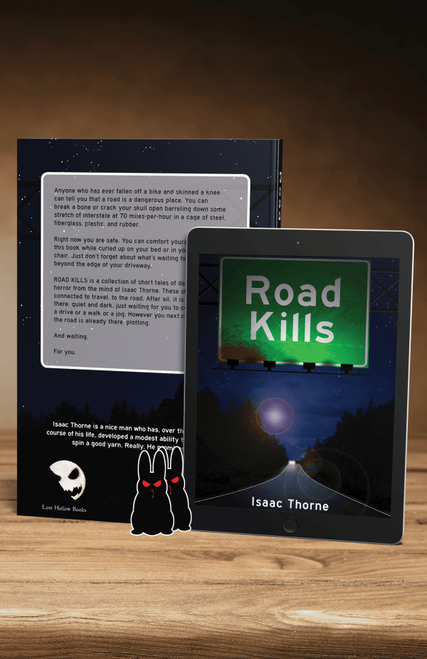 Reverse of the paperback edition of ROAD KILLS and an iPad featuring the cover of ROAD KILLS. Two evil bunny stickers are propped against them.