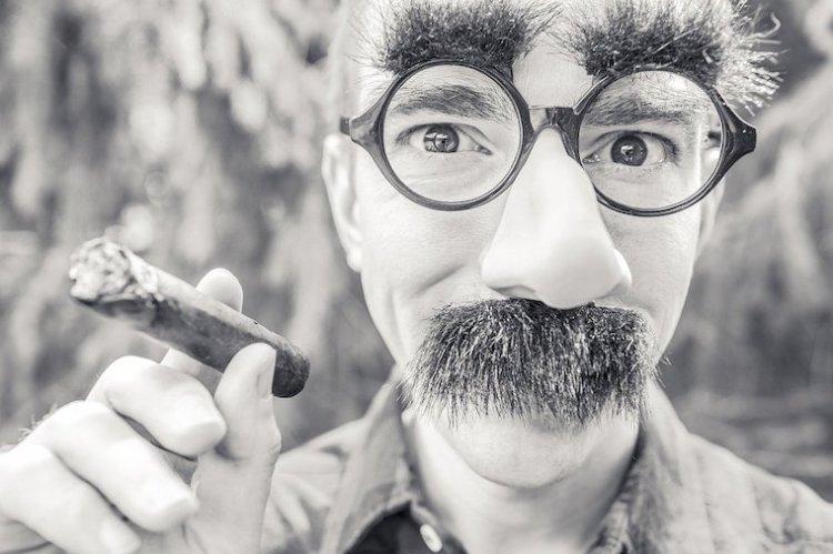 Un homme avec lunette, faux nez et gros sourcils imite Groucho Marx qui brille de tout son talent