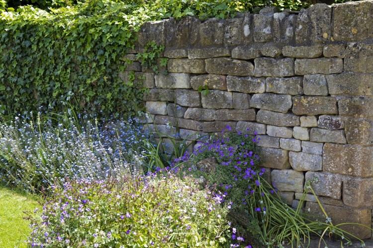 Marcher dans un jardin magnifique complètement entouré d'un mur de pierre