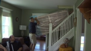 Gordon Hay and Major Paul Blake of the Salvation Army moving a mattress into the house for the family. (CBC)