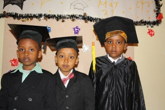 Three boys in front of graduation sign