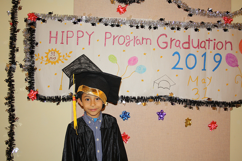 Boy in front of graduation sign