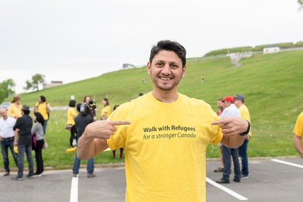 Mohammad Al Masalma smiles for the camera in his yellow shirt at the Walk for Refugees