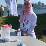 Razan Dervis standing at a table while volunteering at Nova Multifest.