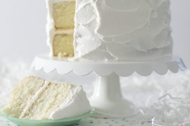 favorite vanilla bean cake on white cake stand with slice cut on a small green plate