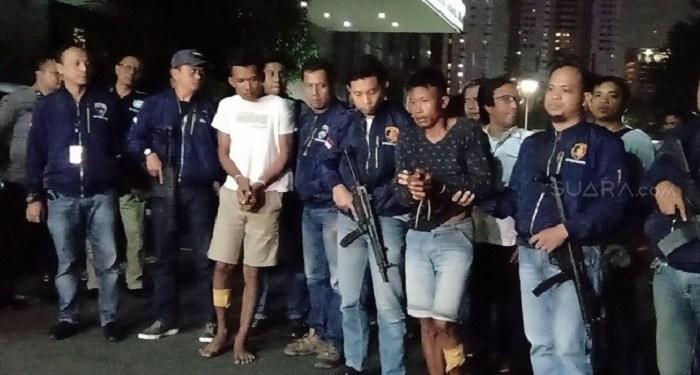 Dua eksekutor pembunuhan terhadap Edi Chandra Purnama alias Pupung Sadili (54) dan M. Adi Pradana alias Dana (23) tiba di Polda Metro Jaya, Selasa (27/8/2019). Foto: Suara