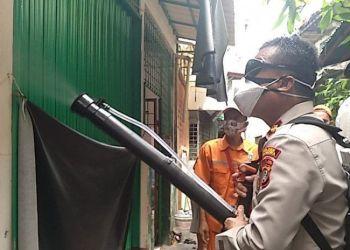 Polisi menyemprotkan disinfektan kawasan mushala jemaah yang terpapar Covid-19. Foto: Antara
