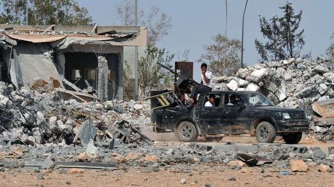 Libyan fighters drive through a destroyed military base used by Muammar Gaddafi's army and subsequently bombed by NATO, southeast of Tripoli, September 2, 2011.