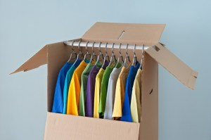 Colorful clothing hanging in a wardrobe box, ready for moving.