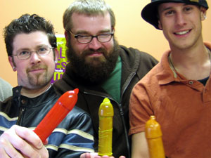 Three men holding coloured external condoms on demonstraters