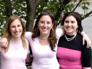 Three females with their arms over each other's shoulders