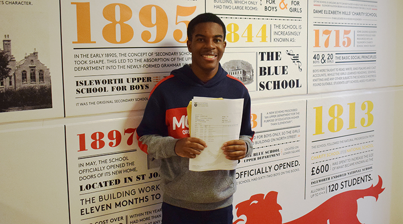 Tinashe Chituku stands with his GCSE results in the main school corridor.