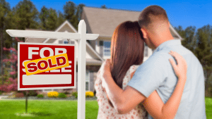 picture of couple looking at house with sold sign