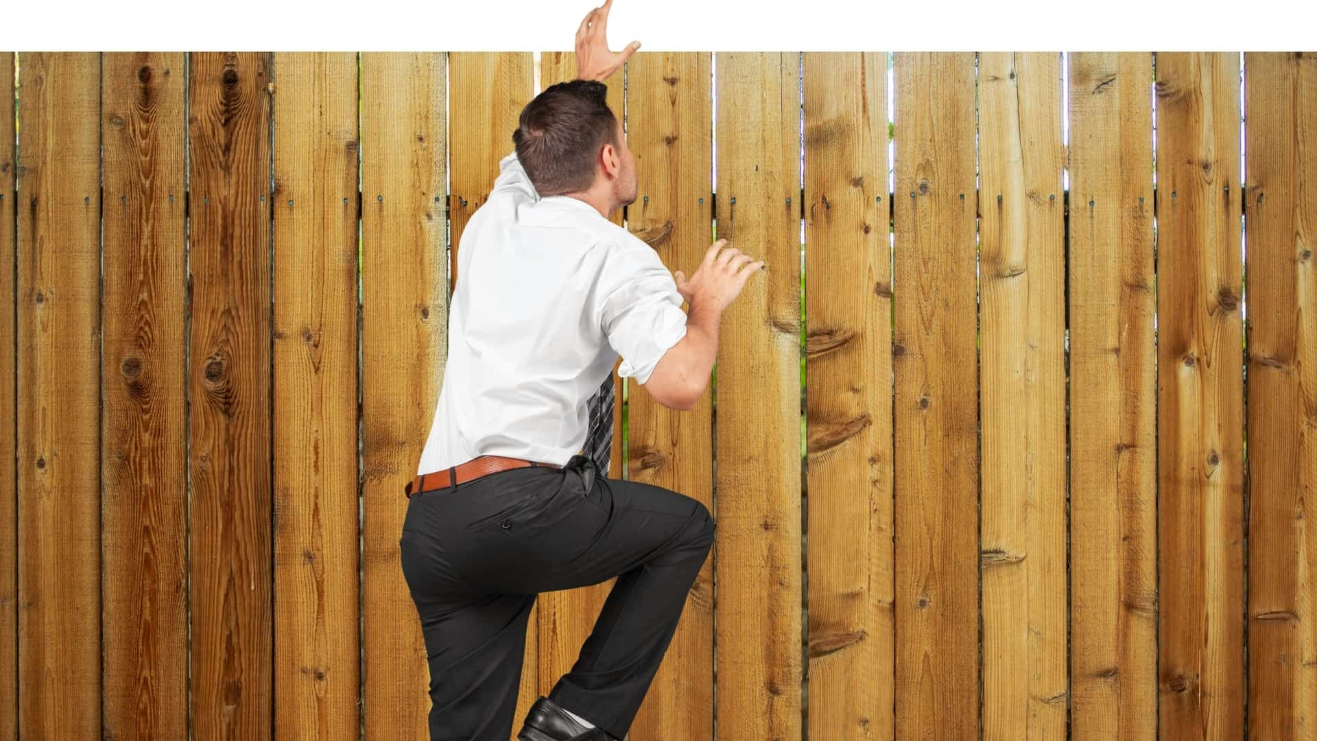 picture of a man climbing a fence