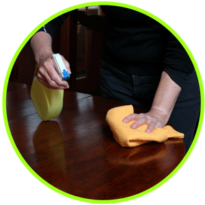 picture of wiping down furniture with cleaner and rag