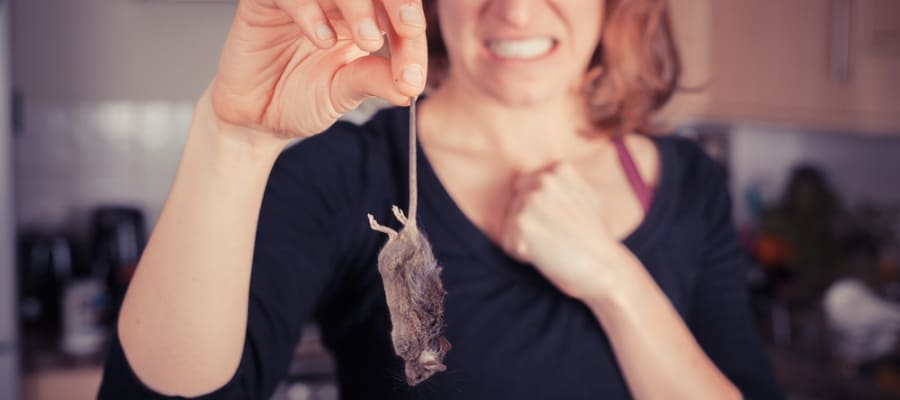 picture of a woman holding a dead mouse by tail