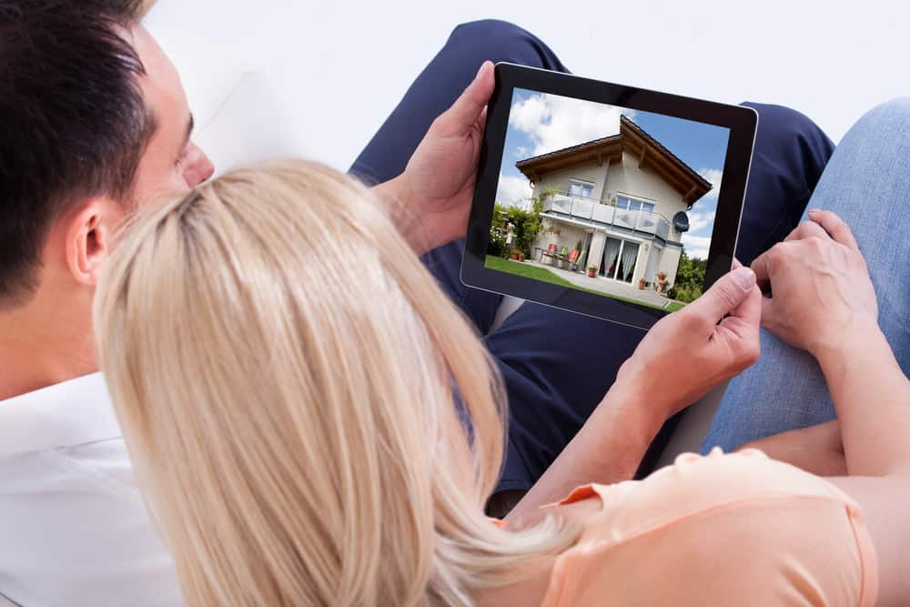 Picture of Couple Looking At House On Digital Tablet's Screen