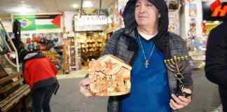 In Bethlehem bus station man asks tourists to buy menorah or creche before Christmas holiday