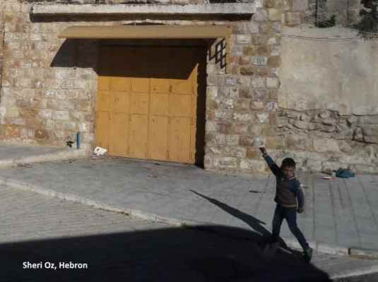 child throwing stones in Hebron
