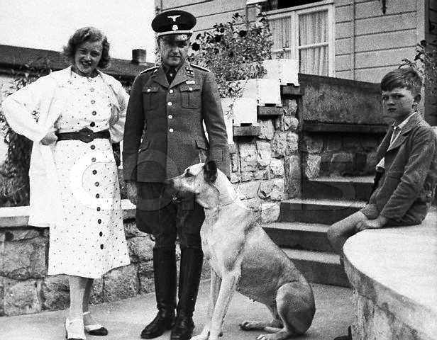 The commandant of the Buchenwald Concentration Camp, SS Colonel Karl Koch stands with his wife Ilsa their son and dog. ca. 1930s-1940s Germany