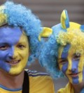 Ukranian soccer fans with painted face in national flag colours smile as they relax in the centre of Donetsk