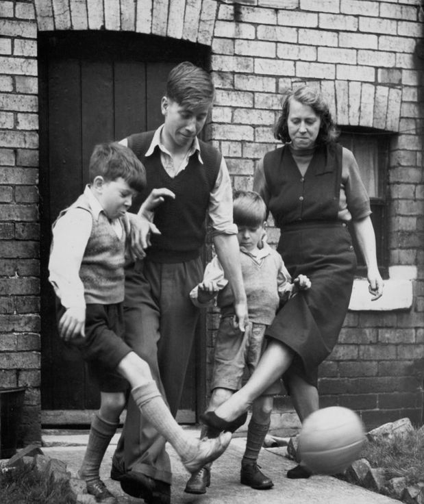 Elizabeth-Charlton-playing-a-game-of-football-with-her-three-sons-Gordon-aged-10-Bobby-15-and-Tommy-7-outside-their-4712684