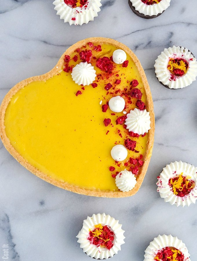 Luscious Yuzu White Chocolate Tart is flavourful, fragrant yuzu lemon and silky white chocolate piped into sweet pastry and topped with freeze-dried raspberry and whipped cream.