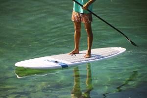 Ein junger Mann beim Paddeln auf einem Paddleboard von TRIPSTIX