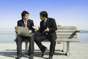 Two business partners working together on a laptop